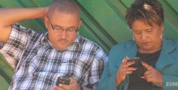 couple-holding-phone-reading-news
